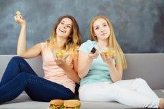 Mujeres jovenes con el telecontrol de la TV que comen los alimentos de preparación rápida fotos de archivo