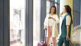 Mujeres jovenes con equipaje en aeropuerto internacional que caminan con su equipaje Pasajeros de la línea aérea en un salón del  metrajes
