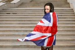 Mujeres jovenes con la bandera de Union Jack contra las escaleras Imágenes de archivo libres de regalías