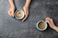 Mujeres jovenes con las tazas de café caliente delicioso en la tabla Imagen de archivo libre de regalías