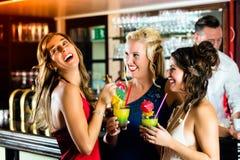 Mujeres jovenes con los cócteles en club o barra foto de archivo