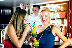 Mujeres jovenes con los cócteles en club o barra imágenes de archivo libres de regalías