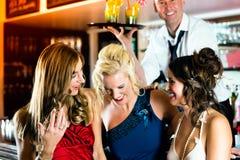 Mujeres jovenes con los cócteles en club o barra Fotos de archivo