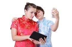 Mujeres jovenes con los dispositivos móviles Fotografía de archivo