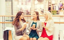 Mujeres jovenes con los panieres y el café en alameda Foto de archivo libre de regalías