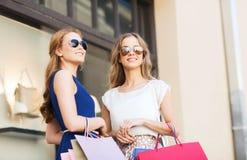 Mujeres jovenes con los panieres y el café en la tienda Imágenes de archivo libres de regalías