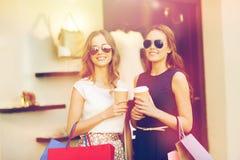 Mujeres jovenes con los panieres y el café en la tienda Fotos de archivo