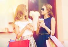 Mujeres jovenes con los panieres y el café en la tienda Imagen de archivo