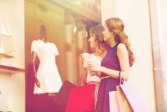 Mujeres jovenes con los panieres y el café en la tienda Imagenes de archivo