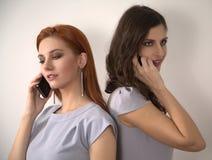Mujeres jovenes con los teléfonos móviles Fotos de archivo libres de regalías