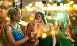Mujeres jovenes con los vidrios de champán en club Foto de archivo libre de regalías
