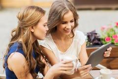 Mujeres jovenes con PC y café de la tableta en el café Imagenes de archivo