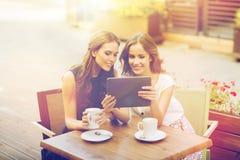 Mujeres jovenes con PC y café de la tableta en el café Fotos de archivo
