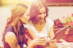 Mujeres jovenes con PC y café de la tableta en el café Imagen de archivo