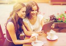 Mujeres jovenes con PC y café de la tableta en el café Imágenes de archivo libres de regalías