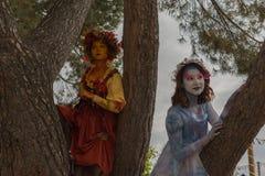 Mujeres jovenes con ropa colorida y la demostración pintada de la cara Fotografía de archivo