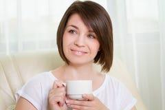 Mujeres jovenes con una taza en casa Imagen de archivo libre de regalías