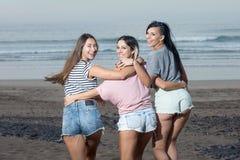 Mujeres jovenes contentas que corren en la playa Fotografía de archivo