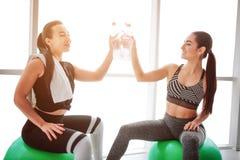 Mujeres jovenes de Haooy cheerfing junto Se sientan en fitballs verdes y botellas de cada uno del tacto Los modelos parecen felic imágenes de archivo libres de regalías
