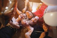 Mujeres jovenes de risa que miran abajo en la cámara que sostiene los globos que tienen partido imagen de archivo