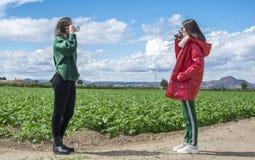 Mujeres jovenes de risa sonrientes que se divierten mientras que bebe el caf? y la charla al aire libre gente, comunicaci?n y ami foto de archivo