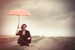 Mujeres jovenes del estilo con el paraguas en el campo Fotos de archivo