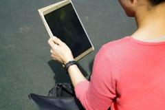 Mujeres jovenes del estudiante que miran la tableta Fotos de archivo libres de regalías