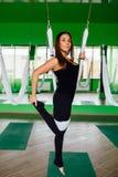 Mujeres jovenes del retrato que hacen ejercicios antigravedad de la yoga Aero- entrenamiento aéreo del instructor de la aptitud d Foto de archivo