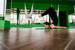 Mujeres jovenes del retrato que hacen ejercicios antigravedad de la yoga Aero- entrenamiento aéreo del instructor de la aptitud d Fotografía de archivo
