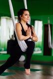 Mujeres jovenes del retrato que hacen ejercicios antigravedad de la yoga Aero- entrenamiento aéreo del instructor de la aptitud d Foto de archivo libre de regalías