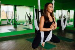 Mujeres jovenes del retrato que hacen ejercicios antigravedad de la yoga Aero- entrenamiento aéreo del instructor de la aptitud d Imagenes de archivo