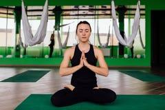 Mujeres jovenes del retrato que hacen ejercicios antigravedad de la yoga Aero- entrenamiento aéreo del instructor de la aptitud d Imagen de archivo libre de regalías