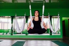 Mujeres jovenes del retrato que hacen yoga antigravedad en la posición de loto Aero- aptitud aérea de la mosca hamacas blancas Imagen de archivo libre de regalías