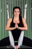 Mujeres jovenes del retrato que hacen yoga antigravedad en la posición de loto Aero- aptitud aérea de la mosca hamacas blancas Foto de archivo libre de regalías