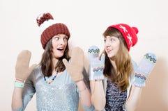 2 mujeres jovenes divertidas en invierno hacen punto el casquillo y los guantes que miran uno a en el fondo blanco Imagenes de archivo