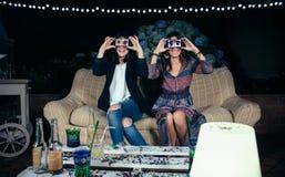 Mujeres jovenes divertidas que sostienen los smartphones que muestran al varón Imágenes de archivo libres de regalías