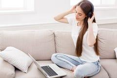 Mujeres jovenes en auriculares que escuchan la música y que usan el ordenador portátil Imagenes de archivo