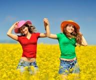 Mujeres jovenes en campo floreciente de la violación Imagen de archivo