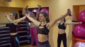 Mujeres jovenes en el club de fitness que hace ejercicios con las pesas de gimnasia, cámara lenta metrajes