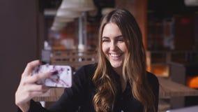 Mujeres jovenes en la camisa negra que toma un selfie de sí misma almacen de metraje de vídeo