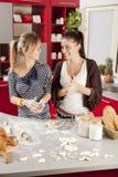 Mujeres jovenes en la cocina Imagenes de archivo