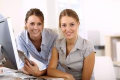 Mujeres jovenes en la oficina que trabaja con la tableta Fotos de archivo libres de regalías