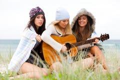 Mujeres jovenes en la playa con una guitarra imagenes de archivo