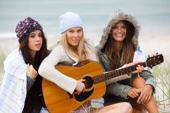 Mujeres jovenes en la playa con una guitarra imágenes de archivo libres de regalías