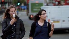 Mujeres jovenes en las calles de Londres con helado almacen de metraje de vídeo