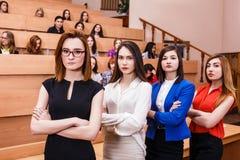 Mujeres jovenes en sala de clase con los estudiantes Foto de archivo libre de regalías