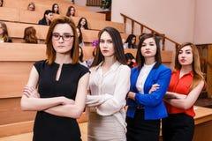Mujeres jovenes en sala de clase con los estudiantes Fotos de archivo libres de regalías