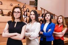Mujeres jovenes en sala de clase con los estudiantes Imagen de archivo