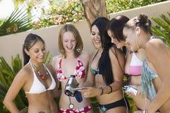 Mujeres jovenes en trajes de baño en el patio trasero que mira la pantalla de la cámara de vídeo foto de archivo libre de regalías