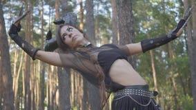 Mujeres jovenes en trajes de los habitantes o de los diablos del bosque que bailan en funcionamiento de la demostración del bosqu metrajes